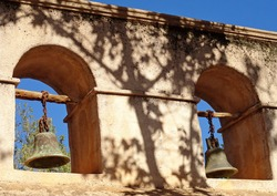 A closeup shot of an old rusted mission bells handing on wooden rods