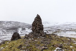 A closeup shot of an old stone cairn in winter landscape in Iceland