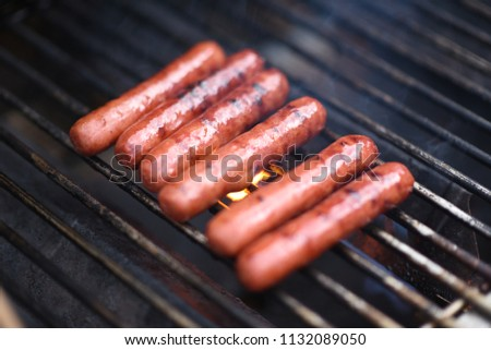 A closeup shot of brats or hotdogs sizzling on a hot grill for a cook out or party.