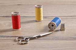 A closeup shot of colorful threads, thimble, and scissors on a wooden table