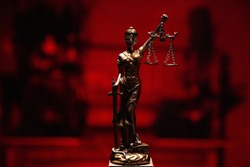 A closeup shot of lady justice bronze statue isolated on a red background