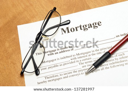 A closeup shot of mortgage papers and glasses to read the fine print.