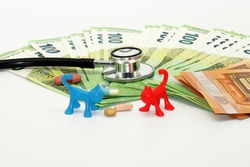 A closeup shot of phonendoscope, euro banknotes, medical tablets, and colorful plastic toys