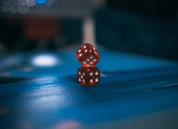 A closeup shot of red dices placed one on another on a blue surface