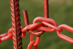 A closeup shot of red plastic barrier chains on rusted metal
