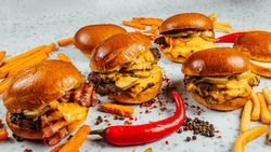 A closeup shot of tasty smash burgers, French fries, and red spicy peppers on the white background
