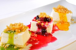 A closeup shot of three pieces of delicious cheesecakes with colorful fruity sauces and berrires