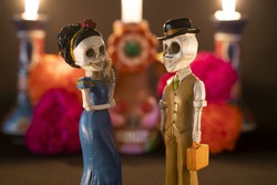 A closeup shot of two skeleton figurines for an offering of the day of the dead on a blurred background