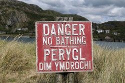 A closeup view of a bilingual red 'Danger no bathing sign' on the edge of the Mawddach estuary, Barmouth, Wales.