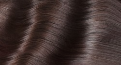 A closeup view of a bunch of shiny straight brown hair in a wavy curved style.