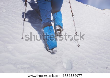 A closeup view of a climber's feet who walks across a filled snow mountain. #1384539077