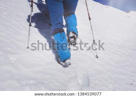 A closeup view of a climber's feet who walks across a filled snow mountain. #1384539077