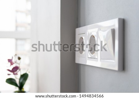 A closeup view of a group of white european electrical outlets and a switch located on a gray wall in a light modern kitchen by the window. Selective focus. Blurred background Сток-фото ©