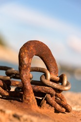 A closeup view of a rusty metal chain secured on a rusty metal hook on a blurry background