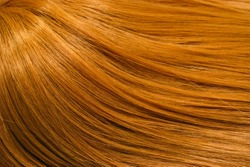 A closeup view of a section of glossy straight ginger hair in a wavy style. Shiny highlight abstract background texture, synthetic extensions. Beauty salon. Hair care, healthy.