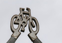 A closeup view of a stylised bicycle above a bike and walking track in Wales, UK.