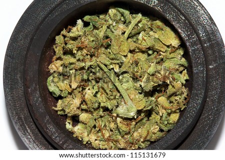 A closeup view of ground up Marijuana leaves in a traditional wooden bowl.