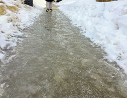 A closeup view of person walking on slippery black ice covering a sidewalk in the early morning of a residential neighbourhood during the winter in Edmonton, Alberta, Canada.