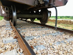 A closeup view of the axle and wheels at the lower end of the railway wagon passing over newly build train track