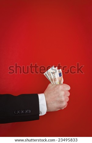 A closeup view of the forearm and hand of a man in a business suit, holding a fist full of paper money against a red background.