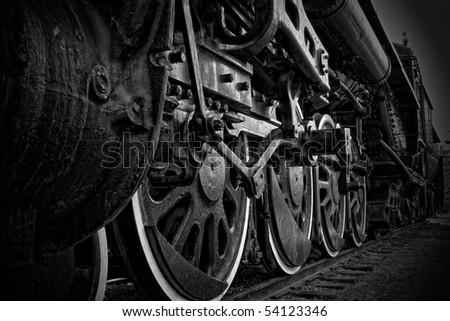 A closeup view of the wheels of an antique steam train, in black and white.