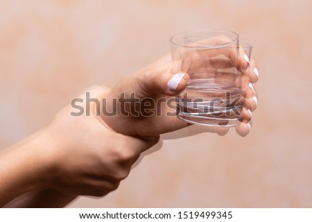 Photo of  A closeup view on the hands of a person trying to hold a glass of water steady, shaking hands symptomatic of a central nervous and motor system disease such as Parkinson's
