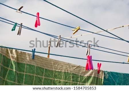 A clothespin hangs on the washing line. A rope with clean linen and clothes outdoors on the day of the laundry. Against the background of green nature and sky