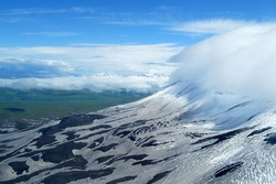 A cloud is hanging low on the slope of a volcano with a backdrop of snowcapped mountains in Kamchatka, Russia