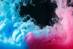 A cloud of colored acrylic paint in water. A drop of colorful ink dissolves in water on a black background. Abstract background.