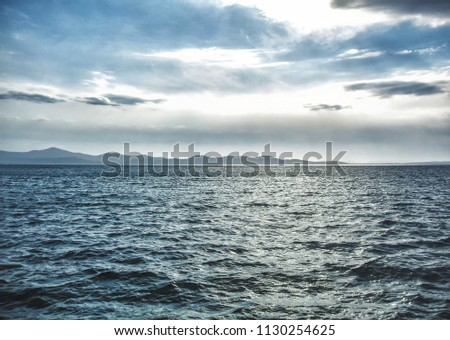 A cloudy day on the wavy sea with a view of the mountains