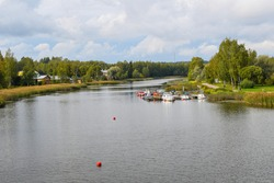 A cloudy early autumn day with boats, dock, homes and a park along the Porvoonjoki River in Porvoo, Finland.