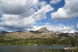 A cloudy filled sky on a summer afternoon at Wet Meadows Reservoir with Raymond Peak in the background.