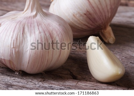 a clove of garlic and a whole wooden table closeup