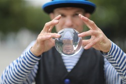 A clown man with a transparent magic ball in his hands on the street of a European city