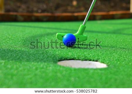 A club prepares to hit a ball during a mini golf game