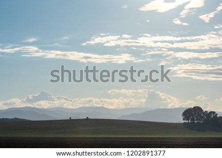 A clump of trees is silhouetted on a green hill with a strip of dirt field in the foreground, blue mountains in the background under a hazy sky brushed with clouds.