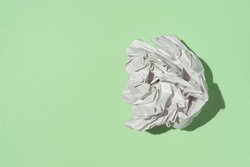 A clump of white paper on a light green background