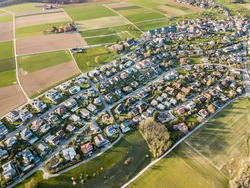 A cluster of houses in the suburban surrounding by fields by aerial drone photogrpaphy