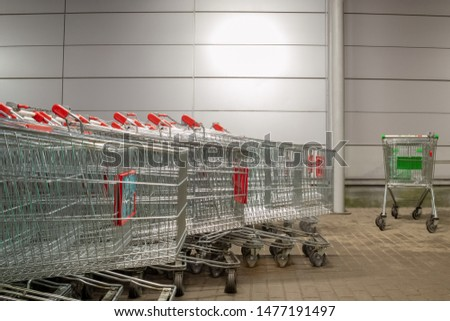 A cluster of identical shopping carts. Aside from them is a single cart of a different color. The concept of individuality, leadership, independence. #1477191497