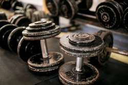 A clutter of heavy, rusty dumbbells in front of a dumbbell rack. A mess of weights at the gym.