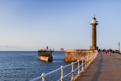 A coastal panoramic view across Whitby harbour and pier. The beautiful blue water and sky at sunset. show the prehistoric coastline with its iconic Whitby Abbey.