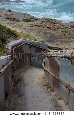 A coastal stairway with rusted railings and a splotchy paint job leading down to the rocky shoreline and the sea