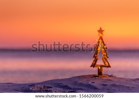 A coastal summer Christmas in Australia.  A driftwood Christmas tree decorated with fairy lights on the beach in summer sunrise or sunset