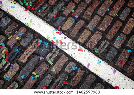 A cobbled road with a white line painted upon it is covered in colourful confetti