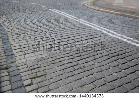 A cobbled street with no traffic now. It is one of the streets of Kolobrzeg in Poland.