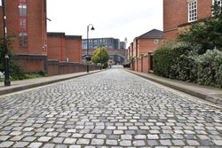 A cobblestone road in a city with modern buildings and a white sky background. Taken in Manchester England.