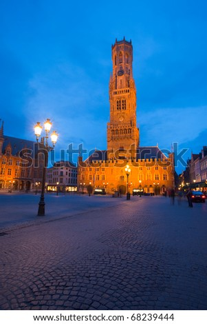 A cobblestone road leads to the belfry and clock tower at twilight blue hour in central old city of Bruges, Belgium