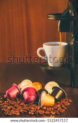 A coffe machine with a cup and coffe capsules and coffee beans in a brown table #1522457117