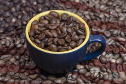 A coffee cup filled to the brim with roasted coffee beans sits in the middle of scattered coffee beans with the texture of an American flag. Concept: American coffee, rich taste, export and import.