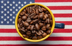 A coffee cup filled to the brim with roasted coffee beans stands on the American flag. Concept: American coffee, rich taste, export and import from America.